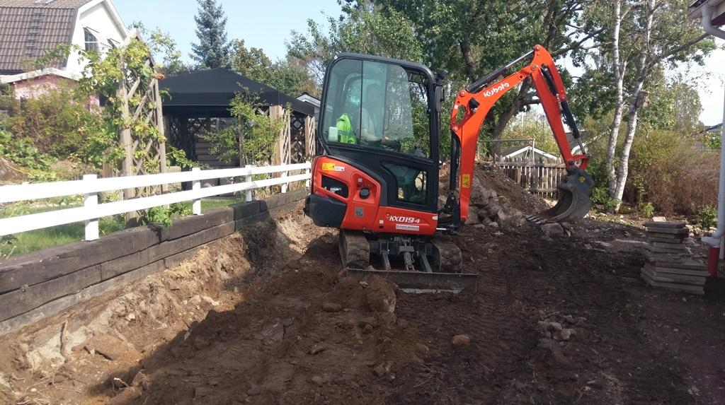 Joel gräver på baksidan och jämnar till och återställer marken.