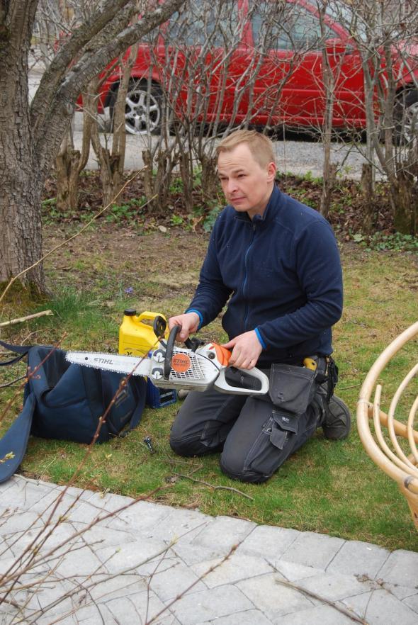 Piotr gör sig själv och motorsågen klar för häckklippning